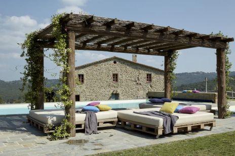 Accanto a alla piscina pergola in legno e divani realizzati con pallet